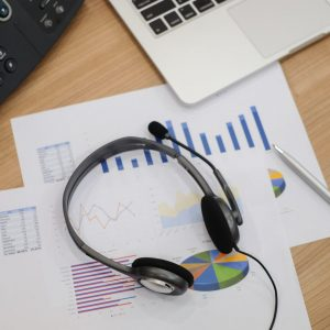 close-up-blurred-of-headset-of-call-centre-at-computer-office-room-with-financial-report-concept-